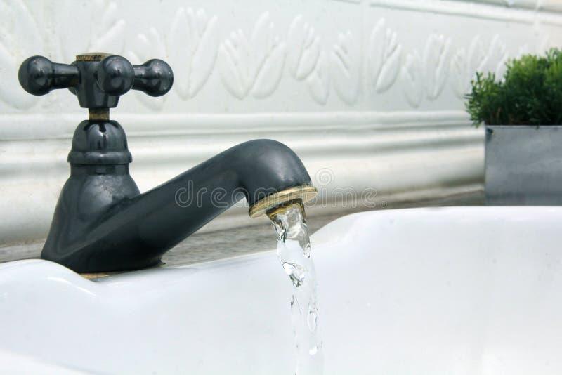 Torneira que vem para fora água no dissipador branco fotografia de stock royalty free