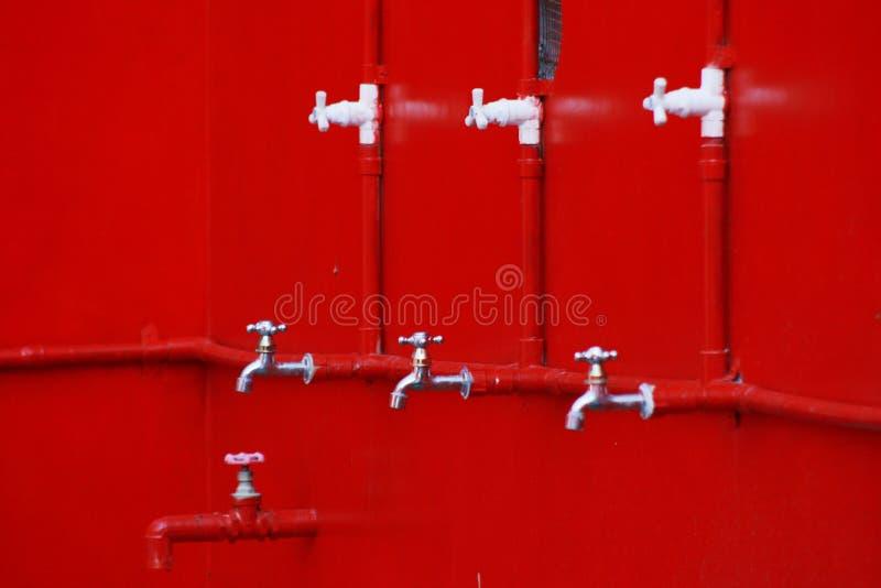 Torneira velha em um vermelho imagens de stock