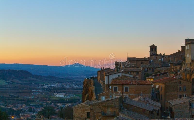 Tornet av en bergstoppstad under solnedgång arkivfoto