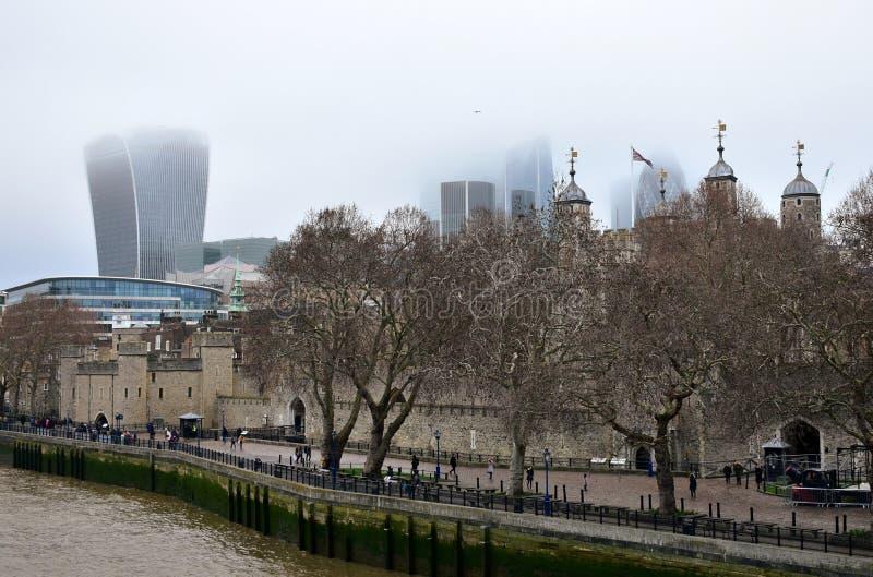 Tornet av London och staden med mist från tornbron Skyskrapor med dimma och Thames River går med träd och folk Lo royaltyfri bild