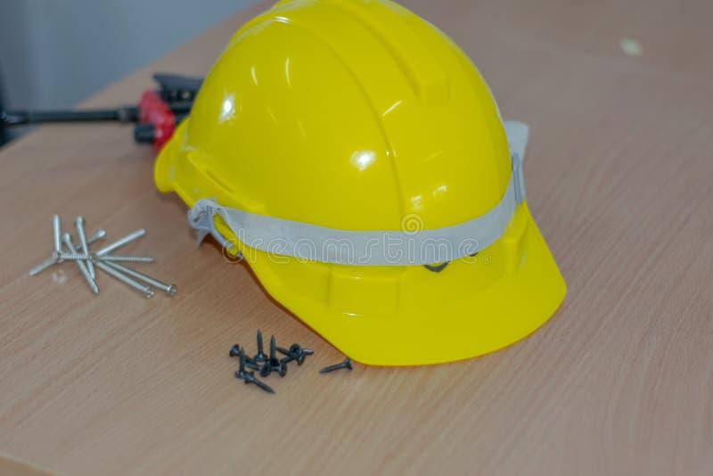 Tornillo amarillo del lanzamiento del sombrero de seguridad colocado en una tabla de madera imagen de archivo