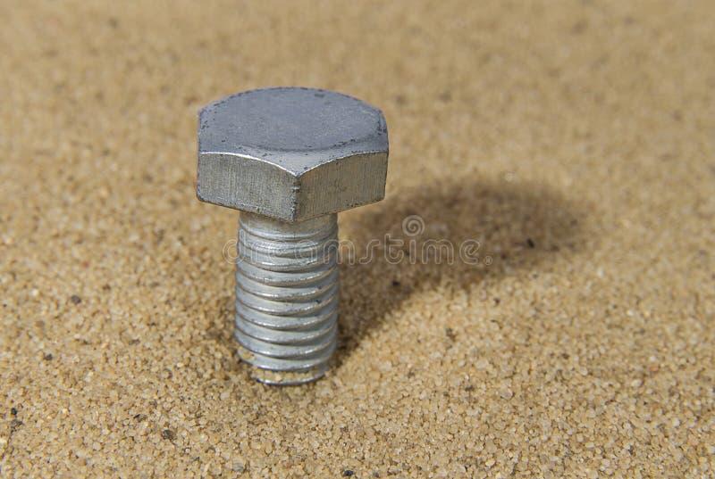 Tornillo de acero en la arena imágenes de archivo libres de regalías
