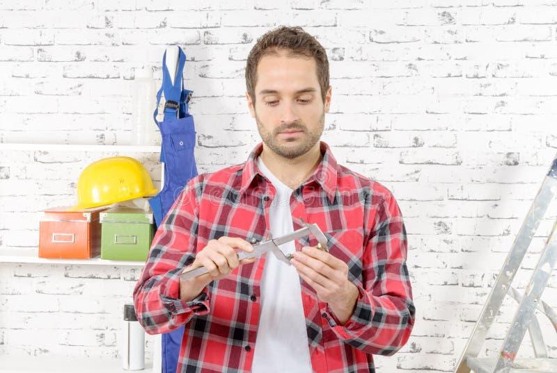 Tornillo de medición del hombre joven usando el calibrador imagen de archivo