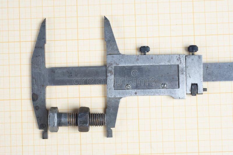 Tornillo, nueces y calibrador en el papel cuadriculado foto de archivo