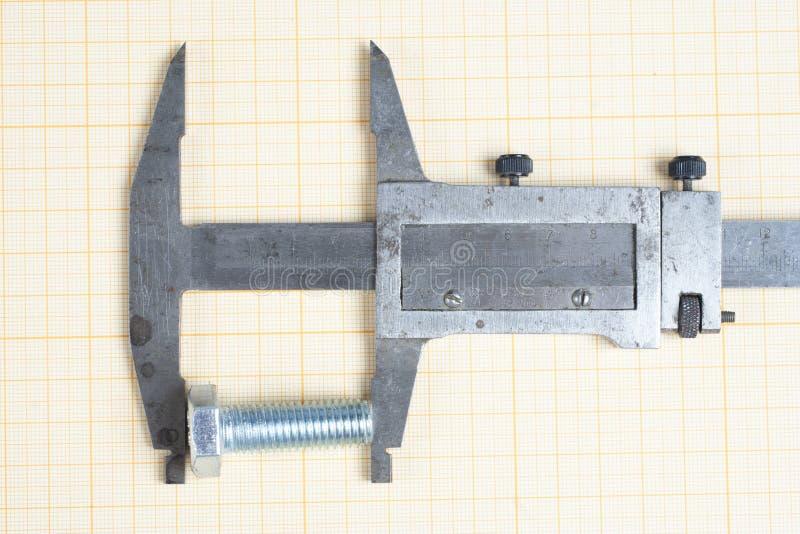 Tornillo, nueces y calibrador en el papel cuadriculado imagen de archivo