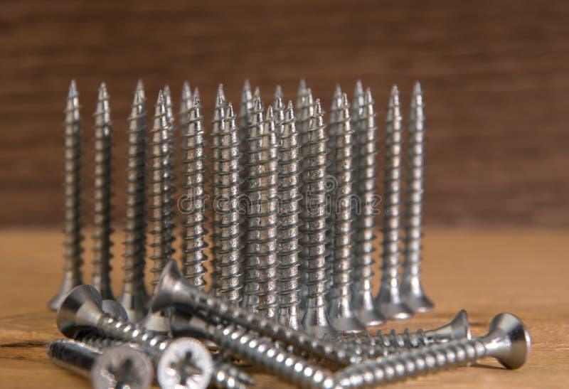 Tornillos de plata universales con un triángulo que señala hacia arriba imagenes de archivo