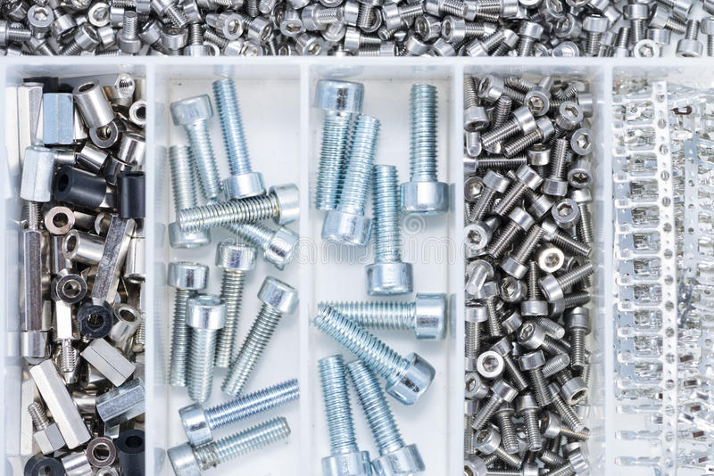 Tornillos y piezas de la máquina en una caja fotos de archivo