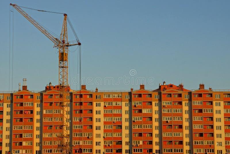 Tornkran framme av ett kvarter av hus mot en blå himmel arkivbilder