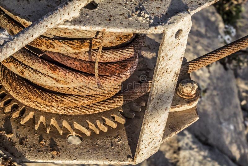 Torno viejo del muelle de la nave con la rueda y Rusty Steel Cable Coil Detail corroídos de engranaje imagen de archivo
