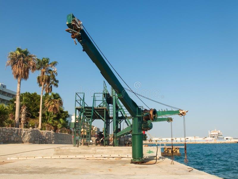Torno viejo que alza el mecanismo en la etapa, las palmas y el mar concretos de aterrizaje del mar foto de archivo libre de regalías