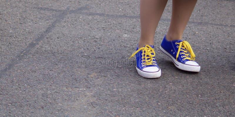 Tornozelos da menina que vestem sapatas azuis dos esportes com la?os amarelos contra o fundo cinzento do pavimento - imagem fotografia de stock royalty free