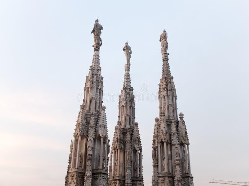 Tornspiror och statyer av Milan Cathedral på solnedgången royaltyfri fotografi