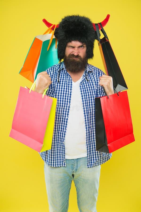 Toro enojado del sombrero del desgaste de la cara del hombre con los cuernos El hacer compras del inconformista adicto o shopahol imagenes de archivo