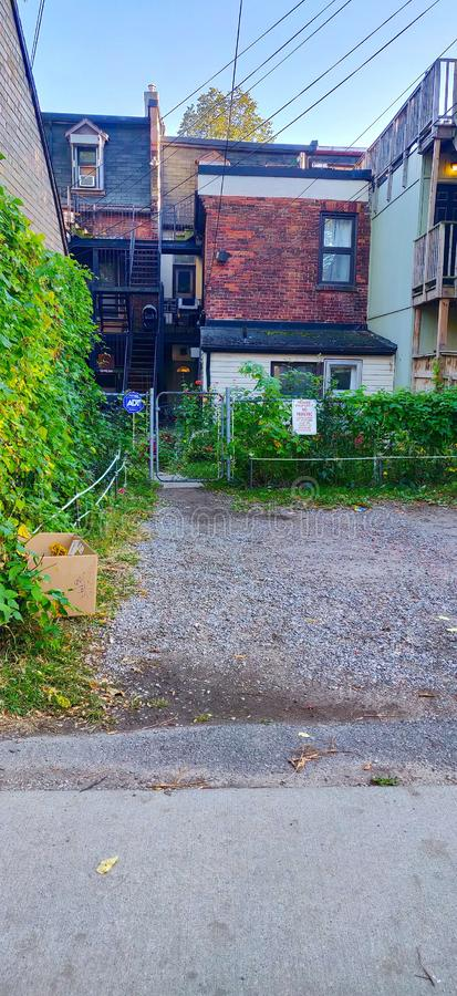 Toronto back alley with view of backyard entrance and gate. Toronto back alley with view of backyard entrance and gate and brick buildings and fire escape royalty free stock photography