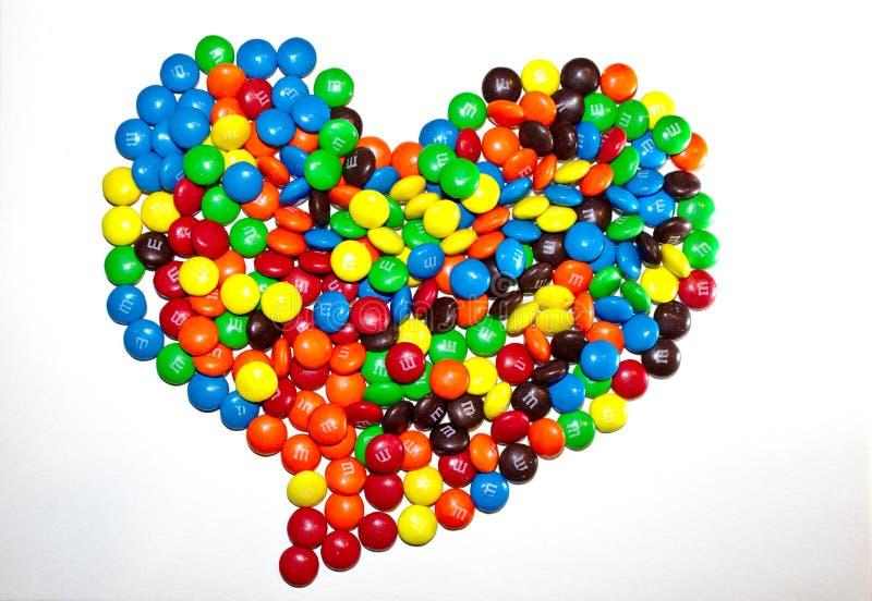 TORONTO, CANADÁ - 10 de marzo de 2017: Una pila en forma de corazón de chocolates revestidos coloridos M&M fotos de archivo