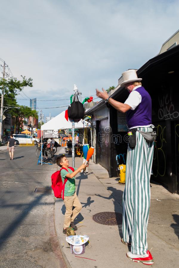 TORONTO, ON, CANADA - JULY 29, 2018: A child watches a street performer at Kensington market in Toronto. stock photo