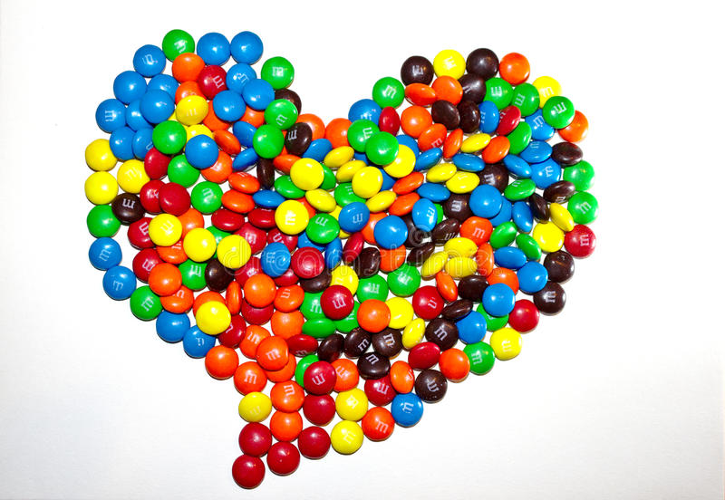 TORONTO, CANADA - March 10, 2017: A heart-shaped pile of colorful coated chocolates M&M stock photos