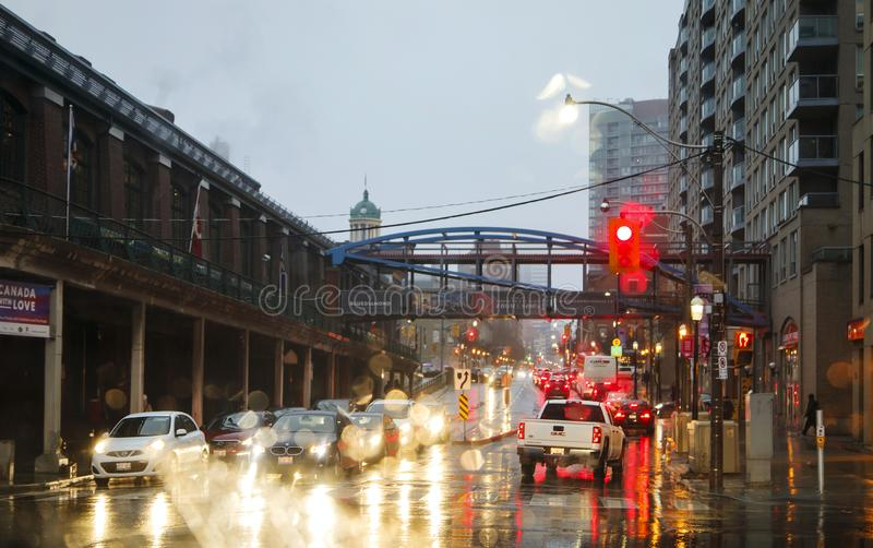TORONTO, CANADA - NOVEMBER 18, 2017: Street in the rain at evening in the light from traffic light and car lights in Toronto Downt royalty free stock photos