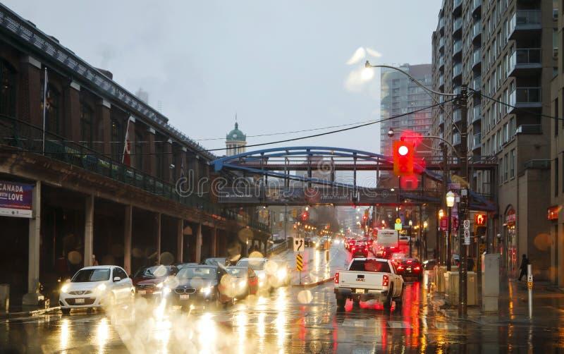 TORONTO, CANADA - 18 NOVEMBRE 2017: Via nella pioggia alla sera alla luce dalle luci del semaforo e dell'automobile a Toronto Dow fotografie stock libere da diritti