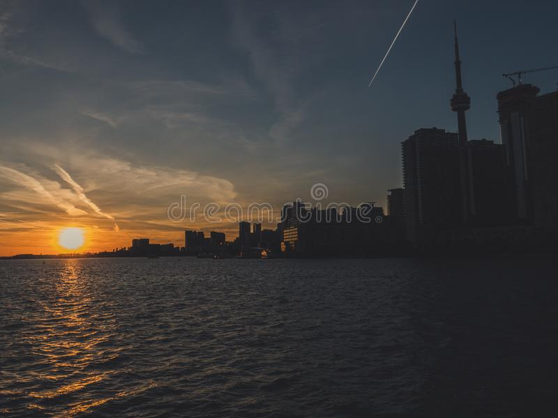 Toronto with cn tower during sunset over lake ontario seen from toronto island ferry royalty free stock images