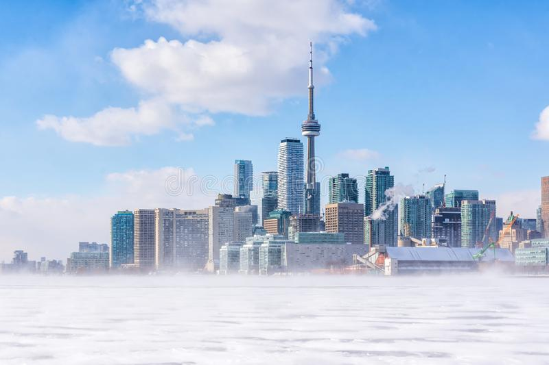 Toronto frozen lake Ontario. Early morning panoramic view of downtown with snow blizzard stock images