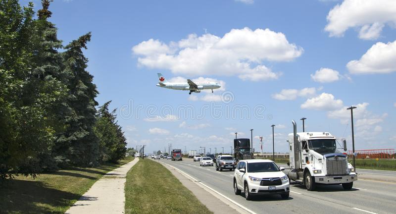 TORONTO - JUNE28, 2018. Air Canada Boeing 737 is landing at Toronto Pearson Airport on June 28, 2018. Airplane flying over the bus. TORONTO - JUNE28, 2018. Air stock photo