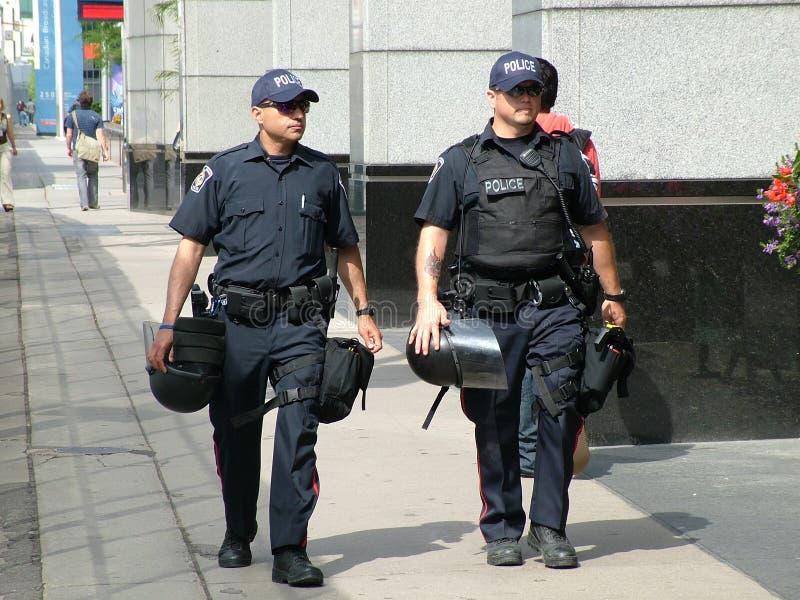 TORONTO - JUNI 23, 2010 - poliser med tumultkugghjulet på gatan före toppmötet G20 i Toronto, Ontario arkivfoton