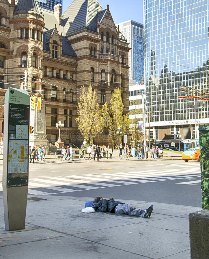 TORONTO KANADA - Maj 13, 2016: Den hemlösa mannen sover på gatan i i stadens centrum Toronto, Kanada royaltyfri bild