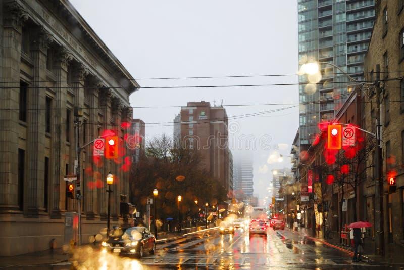 TORONTO, KANADA - 18. NOVEMBER 2017: Straße im Regen am Abend im Licht von den Ampel- und Autolichtern in Toronto Downt stockbild