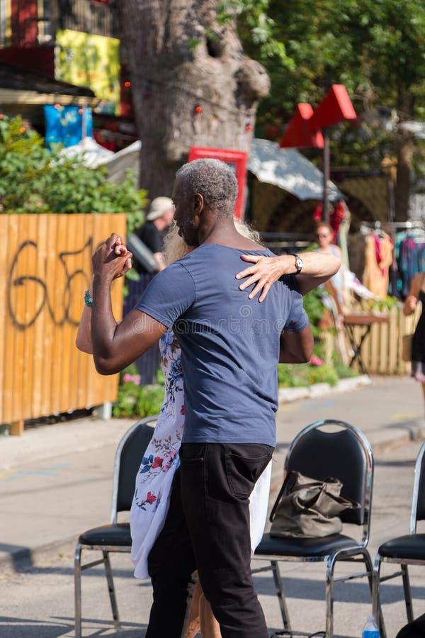 TORONTO PÅ, KANADA - JULI 29, 2018: En mellan skilda raser pardans i gatan på den Kensington marknaden i Toronto royaltyfria foton