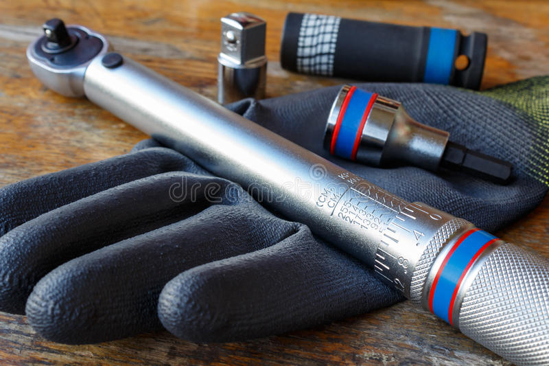 Torque wrench with spanner heads and work glove on the table in a workshop stock images
