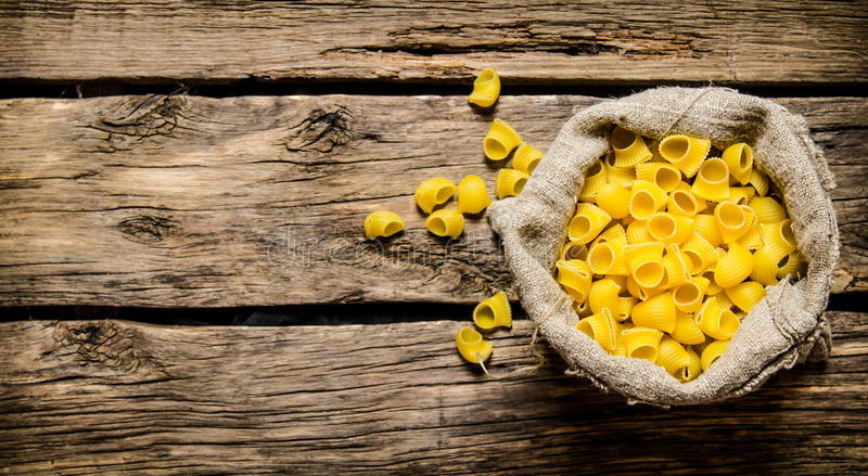 Torr pasta i den gamla påsen På träbakgrund arkivbild