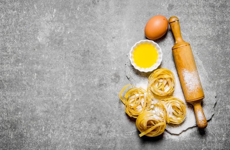 Torr pasta med ägg och kavlen På stentabellen arkivbilder