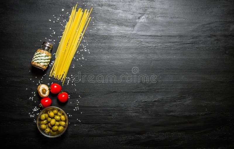 Torr spagetti med oliv, tomater och saltar arkivbild