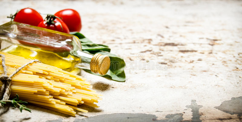 Torr spagetti med olivolja, tomater och örter royaltyfri bild