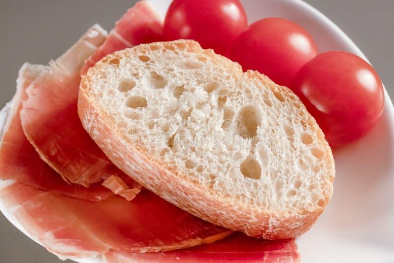 Torr spansk skinka, jamon, italiensk skinka, högg av lager med bröd och körsbärsröda tomater på en vit hjärta-formad platta royaltyfria foton