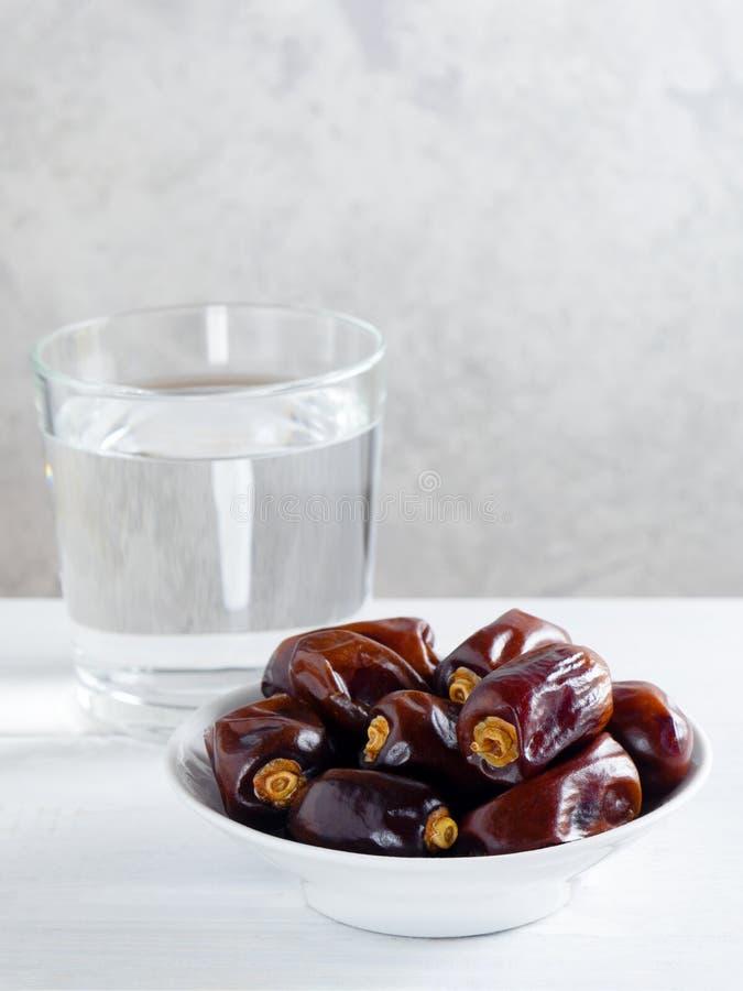 Torra data och ett exponeringsglas av vatten på vit bakgrund Ramadan Iftar matbegrepp fotografering för bildbyråer