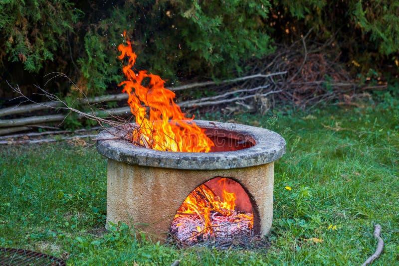 Torra filialer bränner i isolerad lägereldgrop i trädgården Höga ljusa flammor som flimrar på öppen trädgårdbrandgrop royaltyfri foto