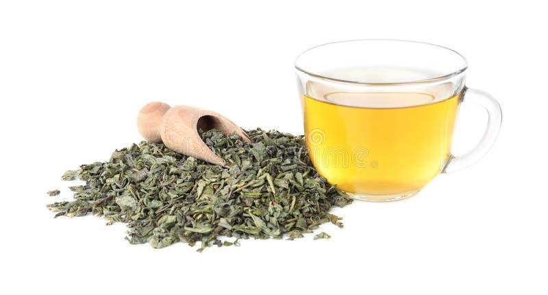 Torra gröna teblad och kopp av den aromatiska drycken på vit bakgrund arkivfoton