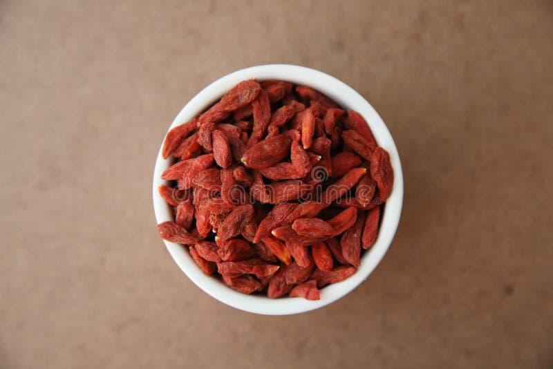Torra röda gojibär på träbakgrund arkivbild