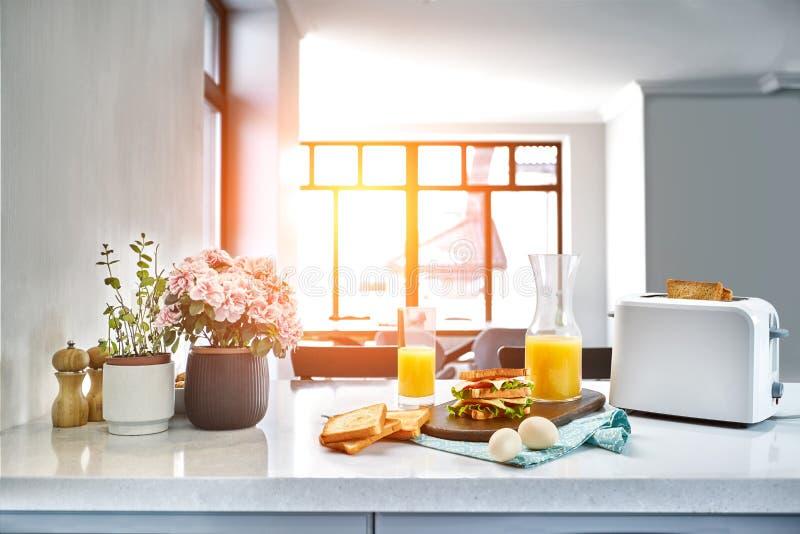 Torradeira elétrico branco do pão com suco de laranja com o sanduíche na mesa de cozinha Café da manhã na cozinha acolhedor Alarg fotos de stock royalty free