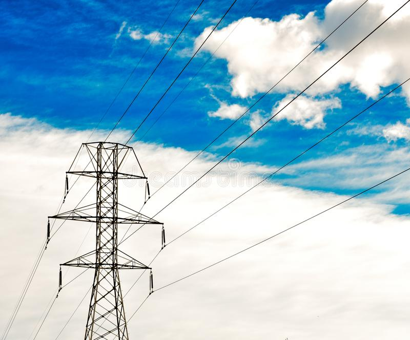 torre ad alta tensione della trasmissione del palo di elettricità con otto cavi su cielo blu nuvoloso Maschera orizzontale fotografia stock
