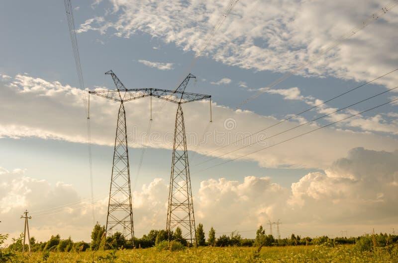 Torre/cargo de alta tensão elétricos da linha elétrica contra o céu azul imagem de stock royalty free