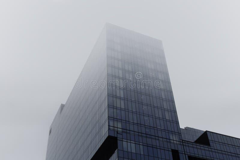 Torre da construção de vidro do arranha-céus moderno na névoa ou na névoa fotografia de stock royalty free