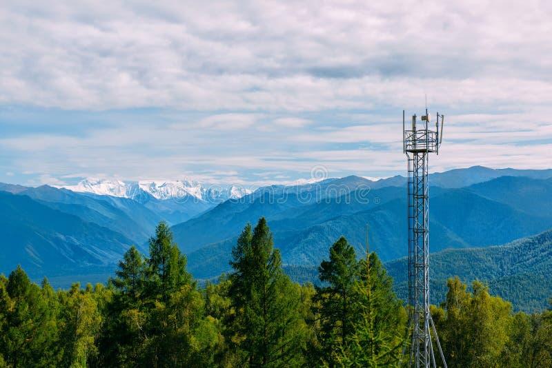 Torre da pilha da telecomunicação na floresta selvagem com fundo da montanha, Altay foto de stock royalty free