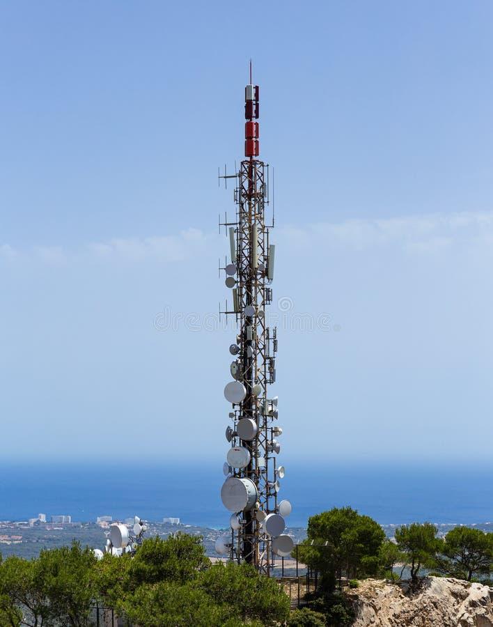 Torre da telecomunicação com antenas celulares em um monte foto de stock