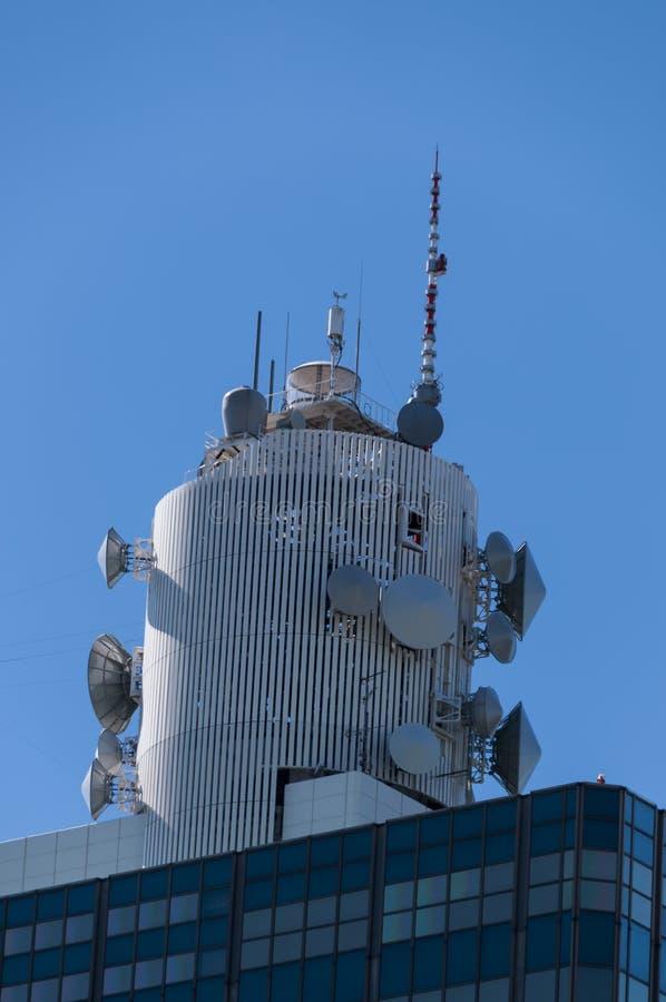 Torre da telecomunicação na parte superior da construção administrativa imagens de stock royalty free