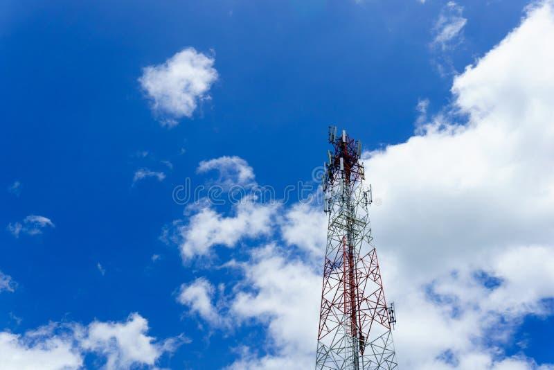 Torre da telecomunicação para a onda de rádio ou celular móvel com o céu azul claro bonito e as nuvens pequenas imagem de stock