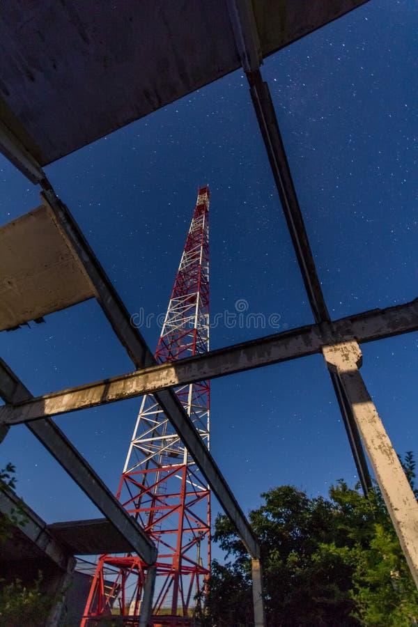 A torre das telecomunicações de estruturas abandonadas contra a noite stars imagem de stock
