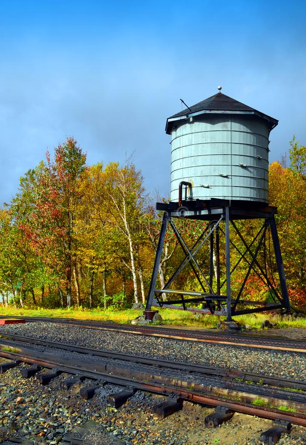 Torre de água ao lado das trilhas do trem fotografia de stock